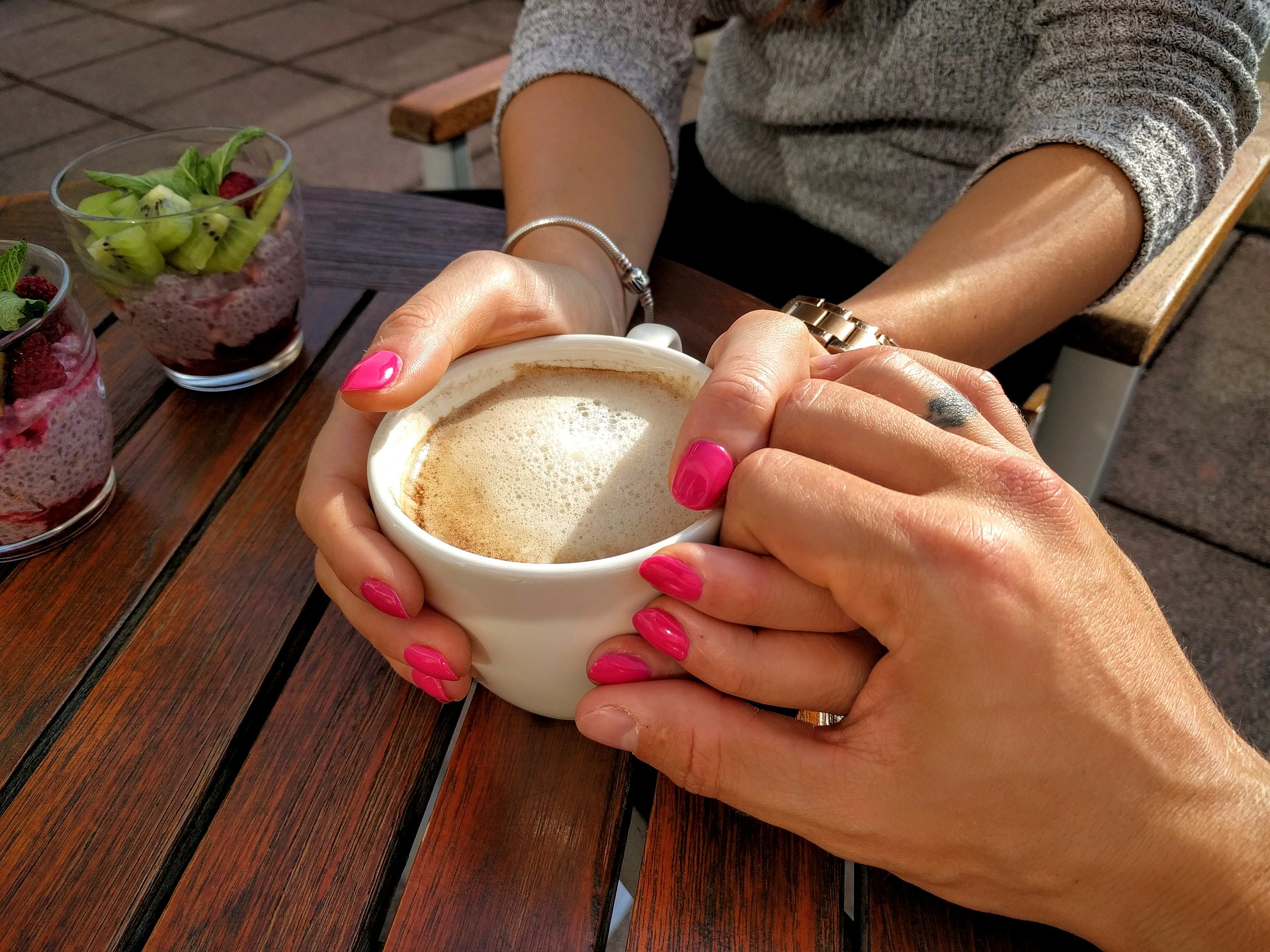 Couple holding hands with coffee
