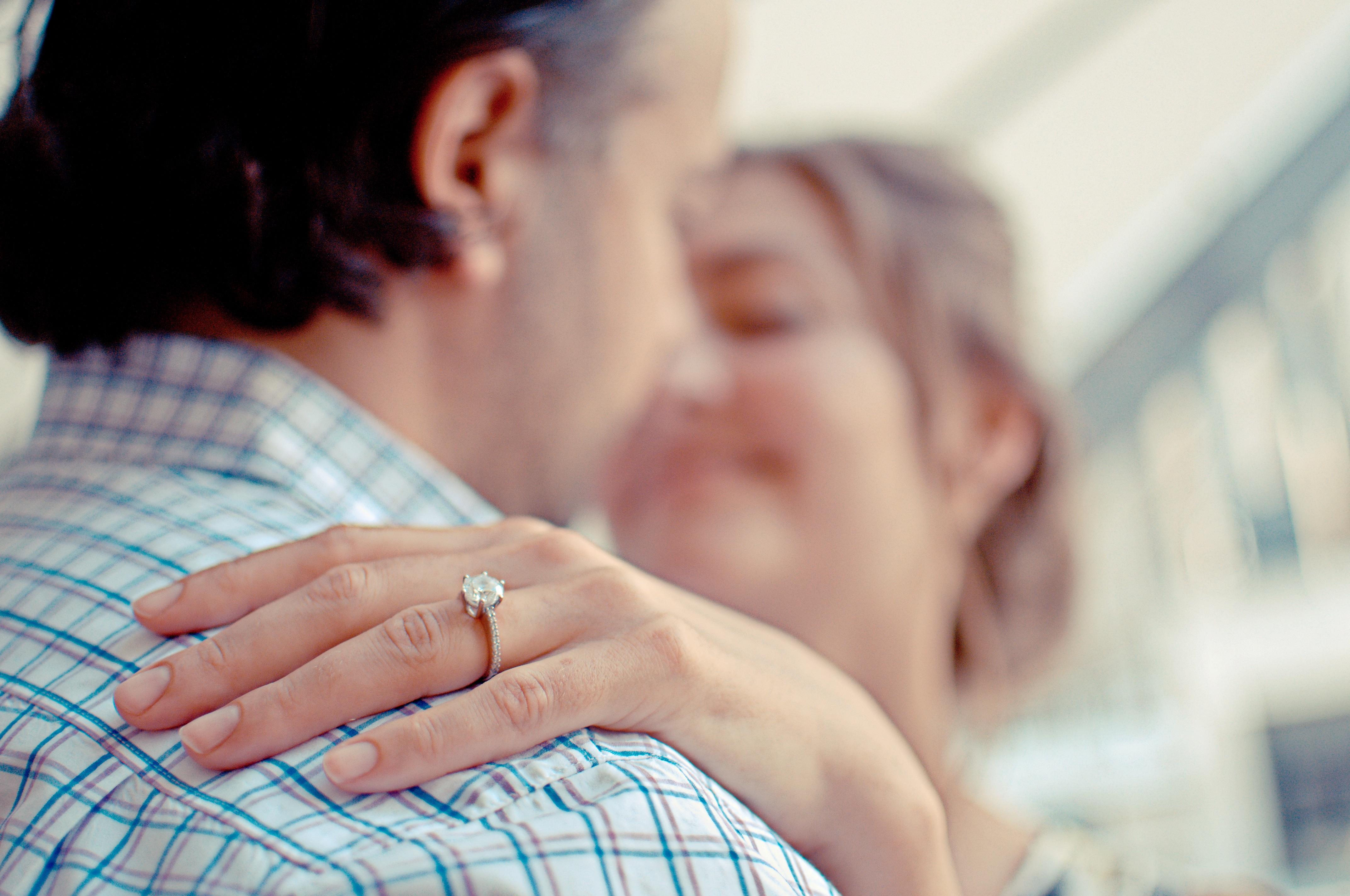 Woman embraces a man wearing a diamond ring
